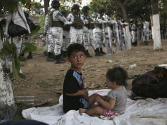 100s in river 'no-man's land' after Mexico troops block way